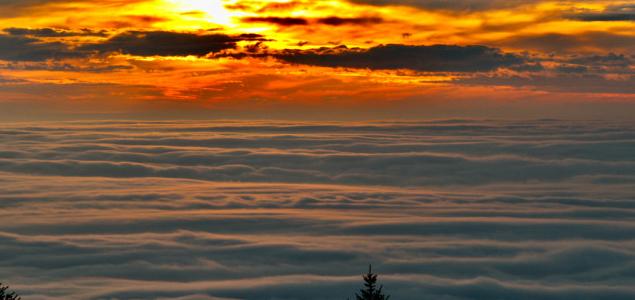 Naplemente a hullámzó ködpaplan fölött